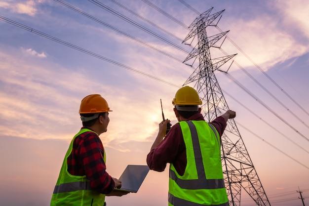 Gerente asiático o engenheiro e o trabalhador em uniforme de segurança padrão trabalham para inspecionar o polo de alta tensão da eletricidade.