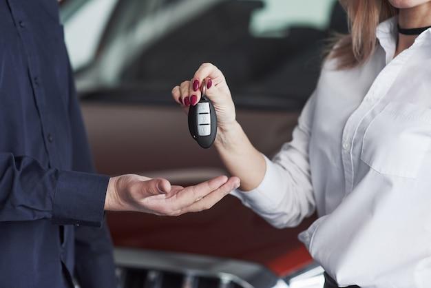 Gerente assistente dando conselhos e ajuda ao cliente em salão de automóveis