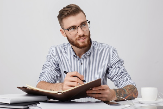 Gerente atencioso com óculos redondos, usa camisa formal, escreve no caderno enquanto está sentado no local de trabalho,