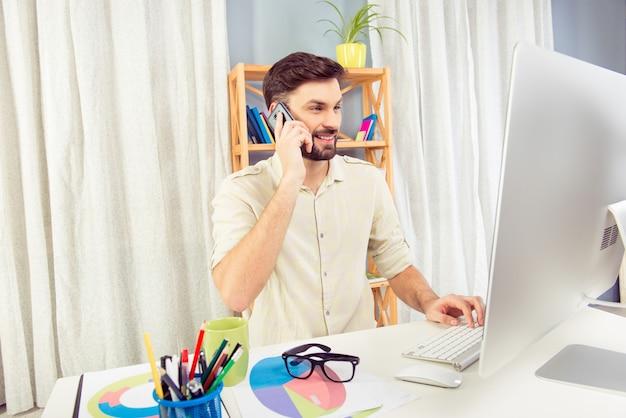 Gerente bem-sucedido e alegre falando ao telefone com seus clientes