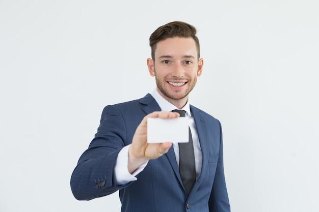 Gerente bonito positivo que mostra o cartão de visita