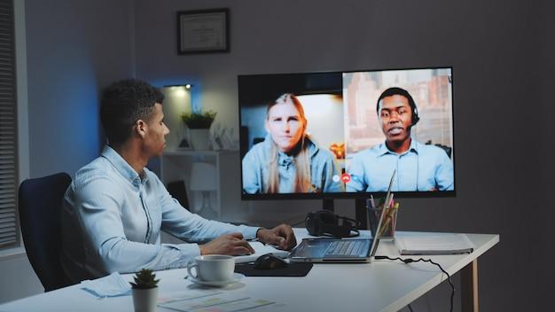 Gerente-chefe preto fazendo vídeo chamada no monitor grande com colegas em quarentena