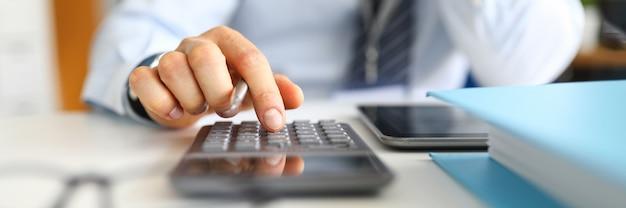 Gerente conta com calculadora sentado no escritório