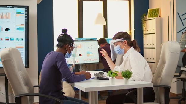 Gerente conversando com funcionário africano sobre estatísticas da empresa usando máscara de proteção e viseira contra coronavírus, sentado à mesa, respeitando a distância social. novo escritório comercial normal.