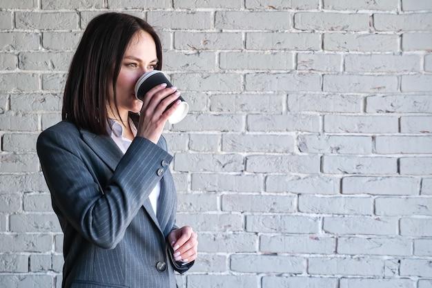 Gerente da empresa sorridente, vestindo blusa e fantasia, bebendo café