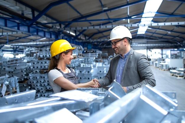 Gerente da fábrica visitando a linha de produção e parabenizando o trabalhador pelo trabalho árduo e bons resultados