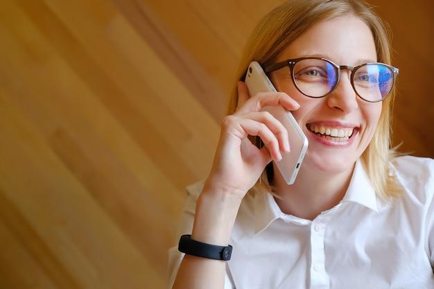 Gerente da menina, freelancer, senhora do negócio com vidros que fala em um telefone móvel, sorrindo.