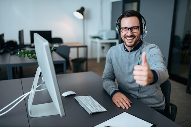 Gerente de apoio técnico masculino alegre que mostra os polegares acima no escritório.