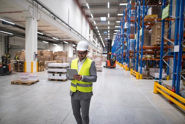 Gerente de armazém caminhando por uma grande área de armazenamento e segurando o tablet enquanto a empilhadeira opera em segundo plano