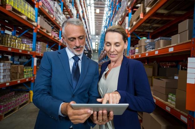 Gerente de armazém e cliente discutindo sobre tablet digital