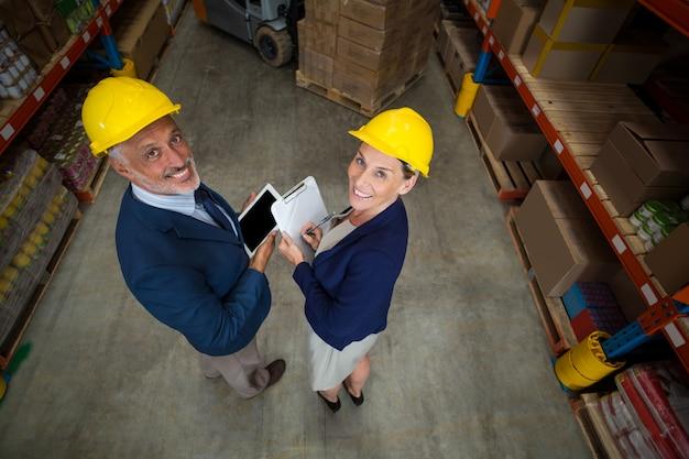 Gerente de armazém e cliente segurando a prancheta e tablet digital