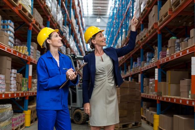 Gerente de armazém e trabalhador, verificando o inventário