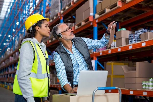 Gerente de armazém e trabalhadora interagindo enquanto estiver usando o laptop