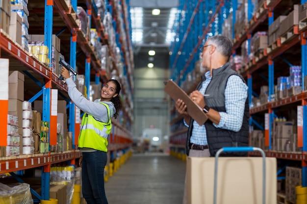 Gerente de armazém e trabalhadora interagindo enquanto trabalhava