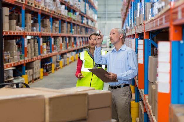 Gerente de armazém e trabalhadora interagindo enquanto verifica o inventário