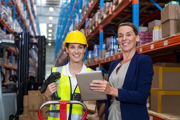Gerente de armazém e trabalhadora sorrindo enquanto segura o tablet digital