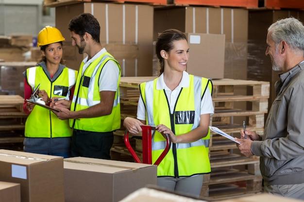 Gerente de armazém e trabalhadores preparando uma remessa
