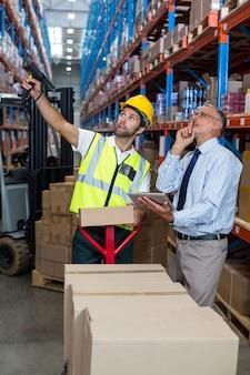 Gerente de armazém interagindo com trabalhador masculino