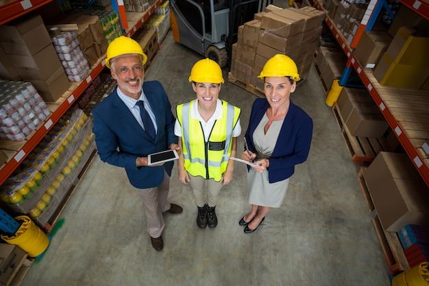 Gerente de armazém permanente com cliente e trabalhador feminino