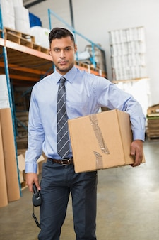 Gerente de armazém, segurando a caixa de papelão e scanner