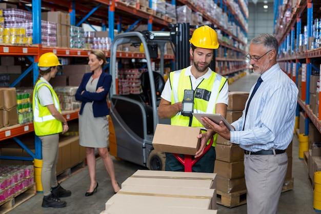 Gerente de armazém, segurando o tablet digital enquanto trabalhador masculino, leitura de código de barras