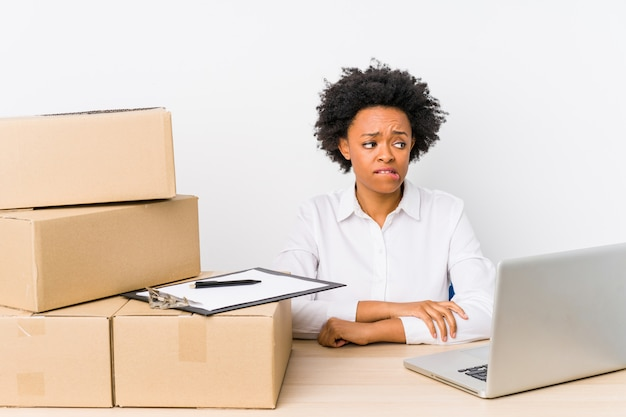 Gerente de armazém sentado verificando as entregas com laptop confuso, se sente duvidoso e inseguro.