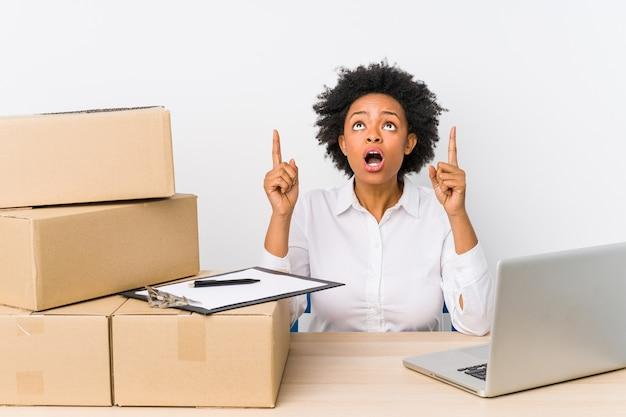 Gerente de armazém sentado, verificando as entregas com o laptop apontando para cima com a boca aberta.
