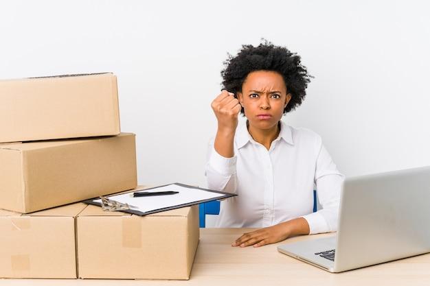 Gerente de armazém sentado, verificando as entregas com o laptop mostrando o punho, expressão facial agressiva.