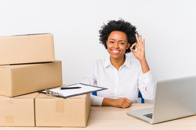 Gerente de armazém sentado verificando entregas com laptop alegre e confiante mostrando o gesto de ok.