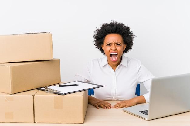 Gerente de armazém sentado verificando entregas com laptop gritando muito irritado e agressivo.