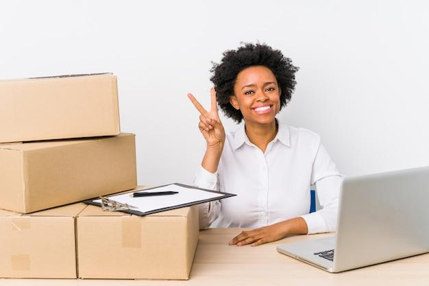 Gerente de armazém sentado verificando entregas com laptop mostrando o número dois com os dedos.