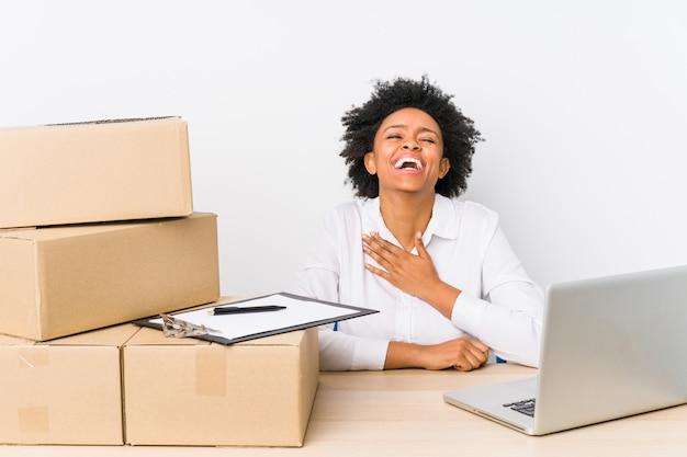 Gerente de armazém sentado verificando entregas com laptop ri alto, mantendo a mão no peito.