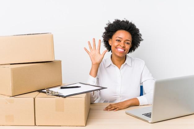 Gerente de armazém sentado verificando entregas com laptop sorrindo alegre mostrando o número cinco com os dedos.