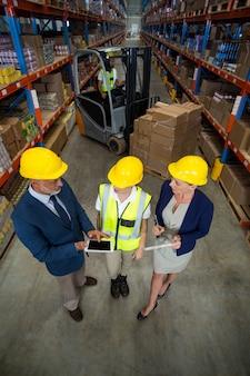Gerente de armazém usando tablet digital com cliente e trabalhadora