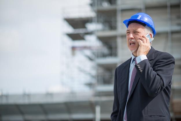 Gerente de arquiteto, falando no celular na frente do canteiro de obras