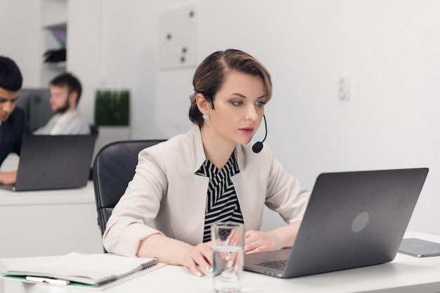 Gerente de atendimento ao cliente no local de trabalho à mesa com um laptop.