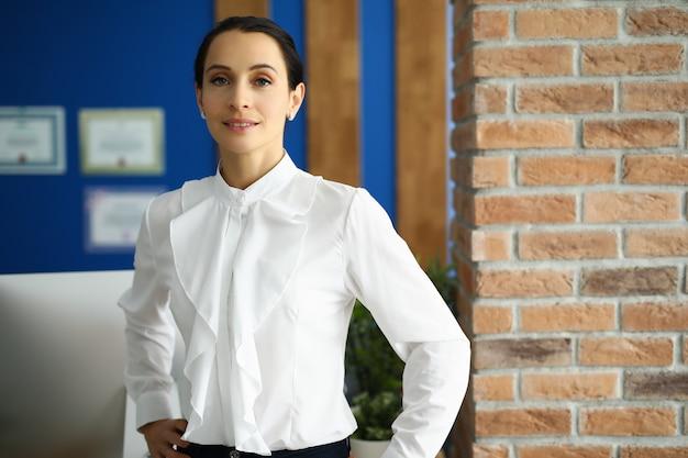 Gerente de blusa branca está de pé no escritório