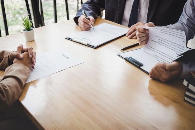 Gerente de comitê de seleção dois lendo um currículo durante uma entrevista de emprego para recrutamento falando