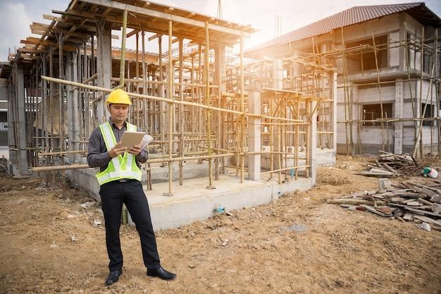 Gerente de construção de homem de negócios asiáticos e engenheiro trabalhador em capacete protetor