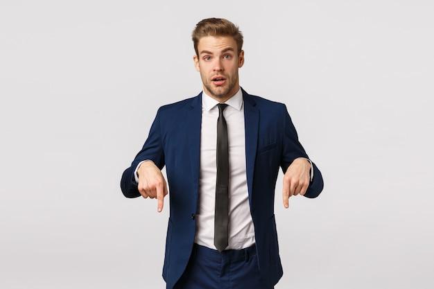 Gerente de consultoria jovem curioso e questionado para novatos, pedindo conselhos, apontando para baixo para fazer perguntas sobre produtos interessantes, o empresário bonito bonito tem algo a oferecer