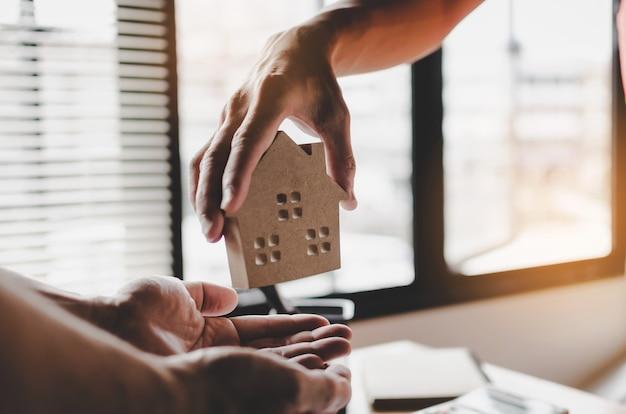 Gerente de corretor de imóveis dando modelo de casa para o cliente