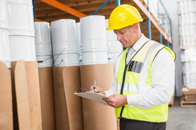 Gerente de depósito verificando sua lista na área de transferência