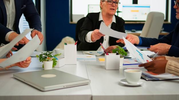 Gerente de empresa confiante dando tarefas de trabalho para diversos funcionários da equipe, analisando a papelada com gráficos sentado no escritório inicial. equipe multiétnica discutindo ideias de projetos em reunião de brainstorming