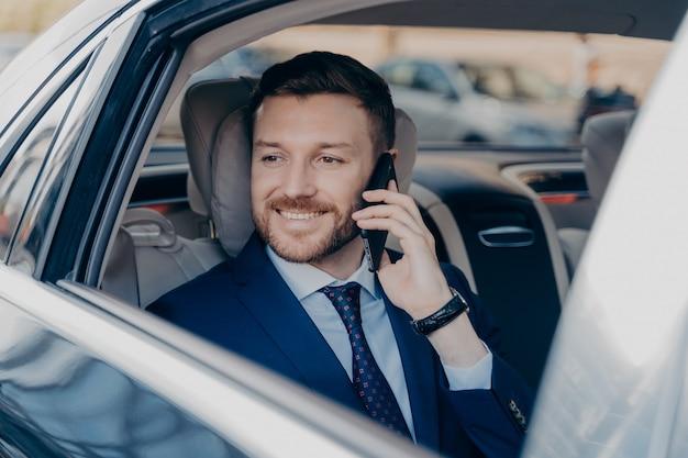 Gerente de empresa feliz ouvindo seu funcionário sobre o tópico de ganho financeiro, ouvindo sobre grandes possibilidades de lucro, pronto para sair e ganhar dinheiro, andando na traseira de um carro de luxo