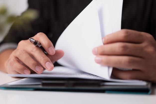 Gerente de empresário com as mãos escrevendo na empresa na mesa do escritório para ler a papelada de assinatura