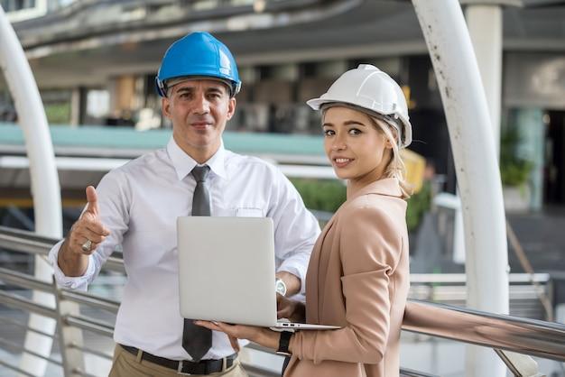 Gerente de engenheiro americano sênior polegares para cima com seu jovem trabalhador sorridente no canteiro de obras na cidade urbana. trabalho em equipe feliz durante o plano de projeto de discussão na cidade moderna.