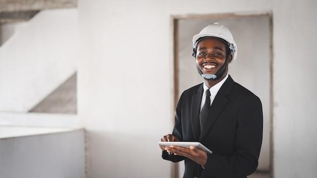 Gerente de engenheiro de construção do homem africano usando tablet e olhando o prédio inacabado