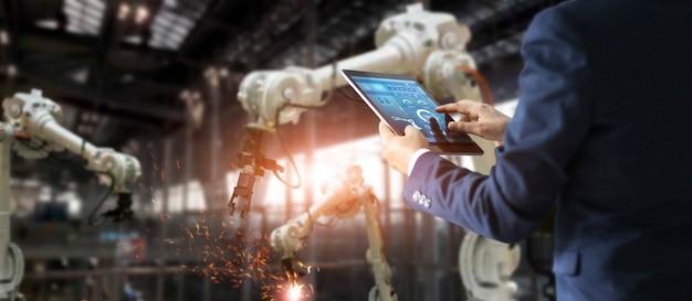Gerente de engenheiro industrial usando a máquina de braços de robô de verificação e controle de automação de tablet