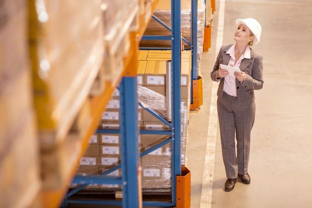 Gerente de entrega profissional olhando para os pacotes enquanto trabalhava no armazém