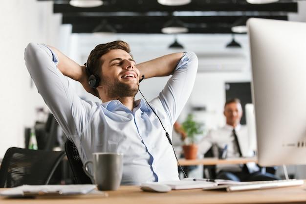 Gerente de escritório alegre falando por fone de ouvido com microfone